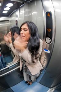 Eine junge Frau mit Klaustrophobie in einem Fahrstuhl